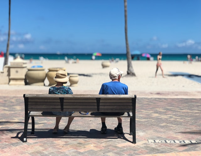 Couple de seniors assis sur un banc, en face de la mer.