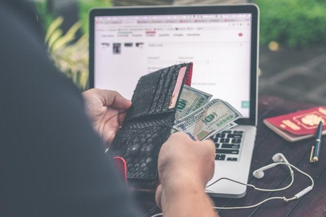 Internaute devant son ordinateur qui sort son portefeuille pour payer une croisière.