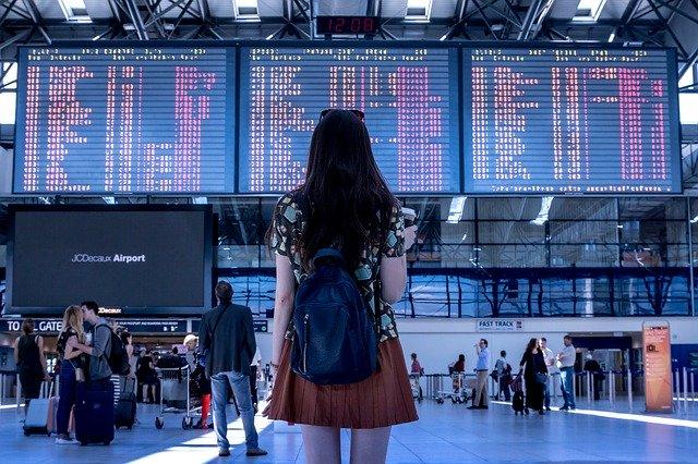 Femme à l'aéroport face aux vols